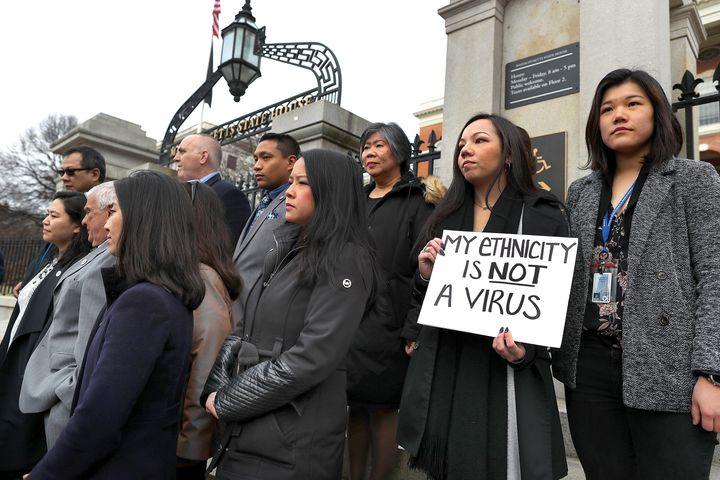 """A protest against anti-Asian attacks. In it, a young woman presents a sign that says """"My ethnicity is not a virus."""""""