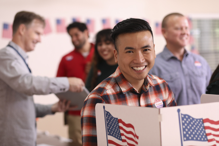 Mid-adult, Asian descent man votes in the USA election. He stands at voting booth in polling station. Other voters and election day registration seen in background.