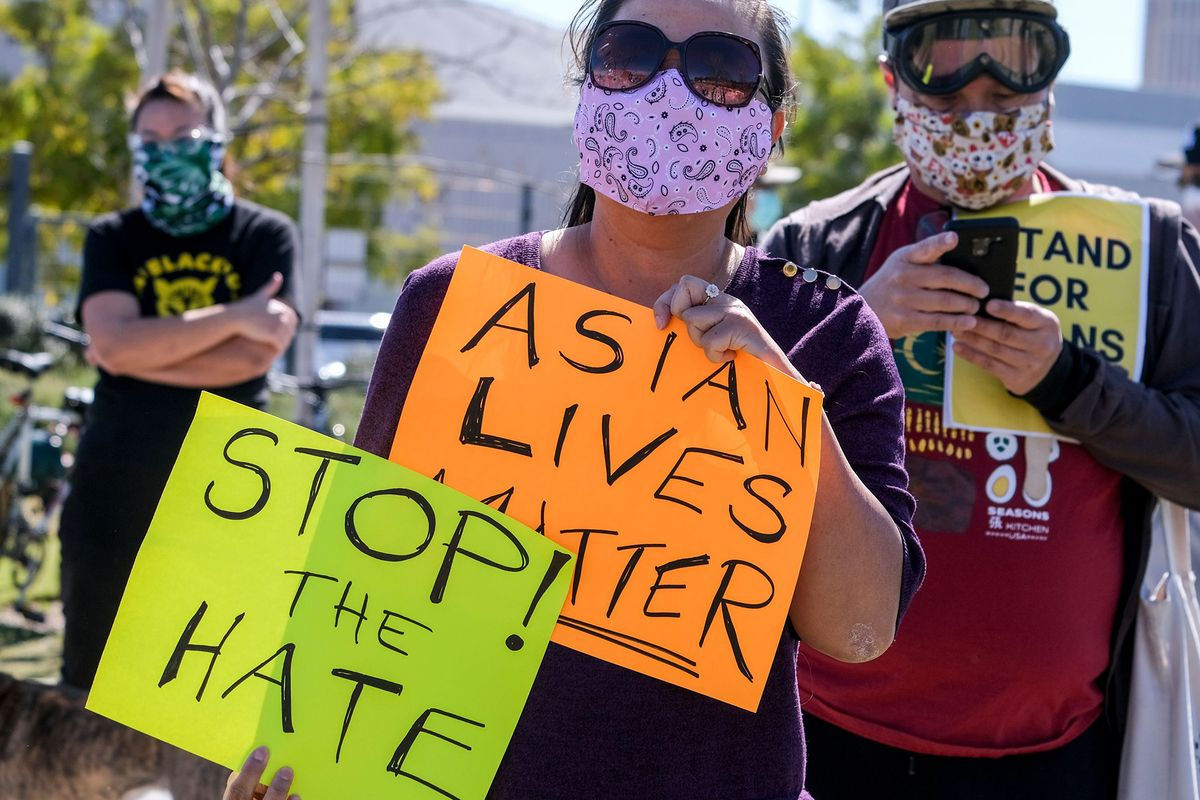 Demonstrators wearing face masks and holding signs take part in a rally to raise awareness of anti-Asian violence, near Chinatown in Los Angeles, California, on February 20