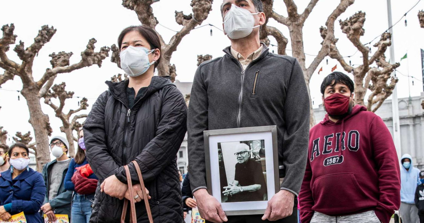 Vicha Ratanapakdee, 84, was assaulted on Jan. 28 while out on a morning walk and later died from head injuries. His son-in-law, Eric Lawson (right), holds a photo of Ratanapakdee as he stands with his wife, Monthanus, while attending a rally on Feb. 14 at San Francisco's Civic Center Plaza in condemnation of the recent increase in violence towards the Asian American community around the Bay Area.