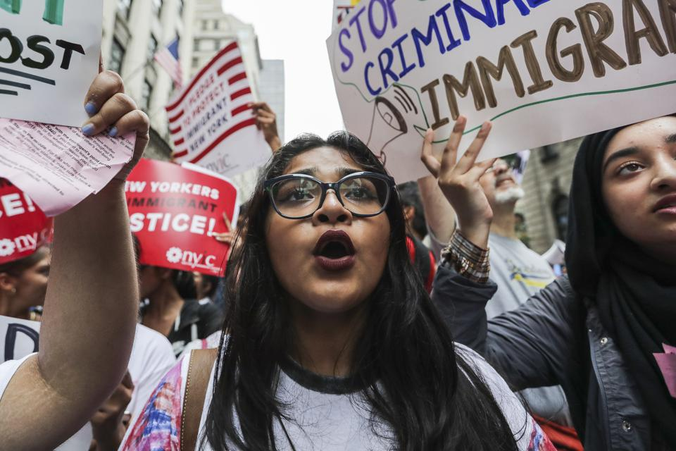 Demonstrators hold signs and chant during a Defend DACA rally.